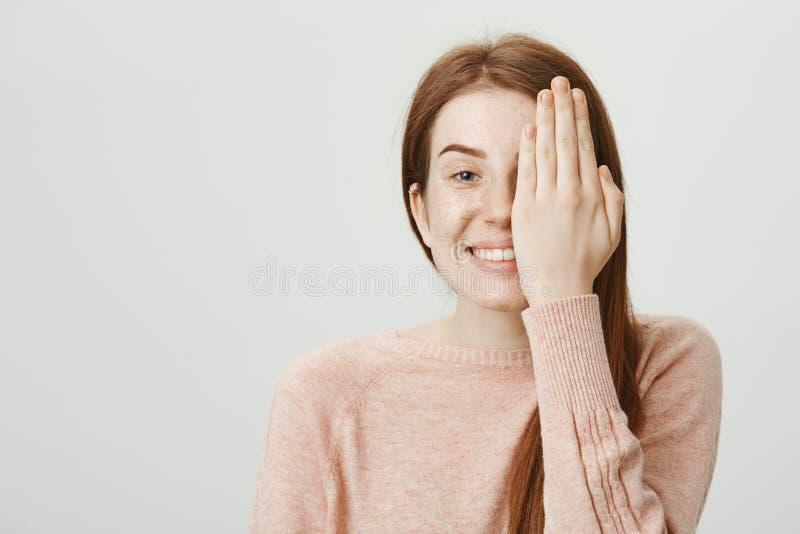 Uśmiechnięta figlarnie caucasian rudzielec z ślicznymi piegami chuje połówkę twarz za palmą, ono uśmiecha się radośnie i stać, obraz royalty free