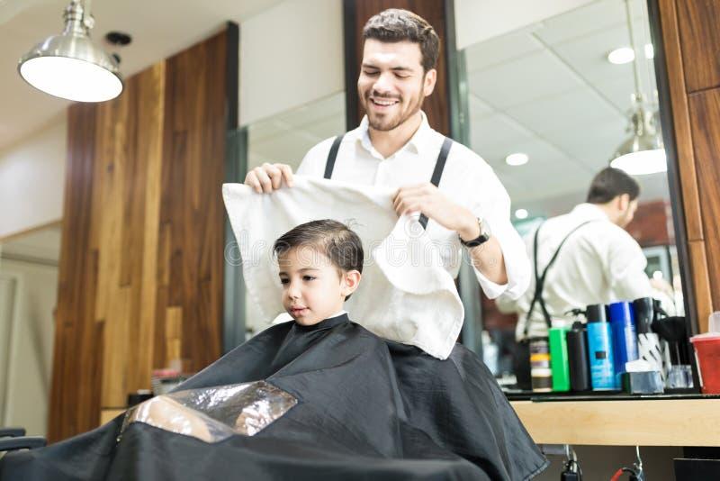Uśmiechnięta Hairstylist obcierania głowa Mały klient W fryzjera męskiego sklepie zdjęcie royalty free
