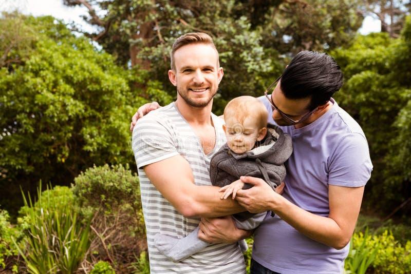 Uśmiechnięta homoseksualna para z dzieckiem zdjęcie royalty free