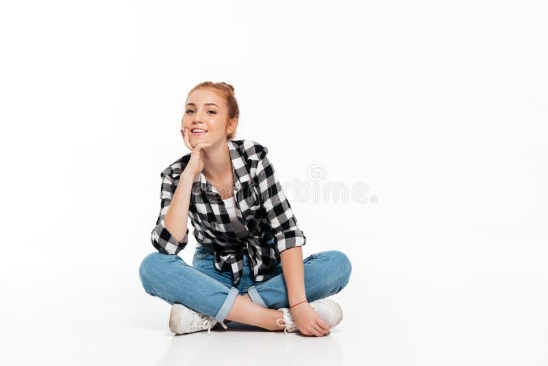 Uśmiechnięta imbirowa kobieta siedzi na podłoga w koszula i cajgach obraz stock
