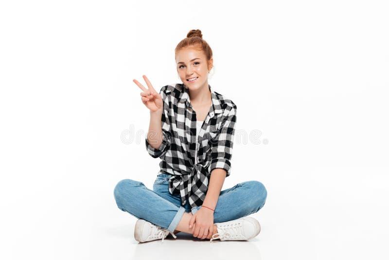 Uśmiechnięta imbirowa kobieta siedzi na podłoga w koszula i cajgach zdjęcie royalty free