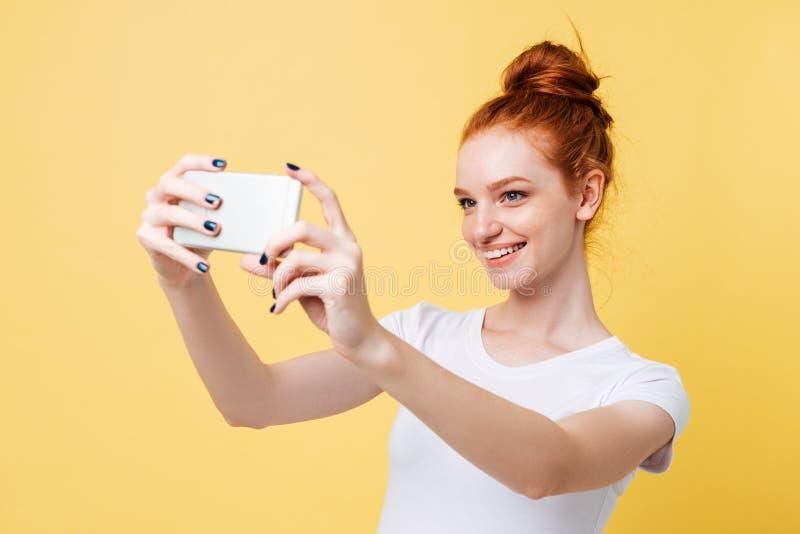 Uśmiechnięta imbirowa kobieta w koszulce robi selfie na jej smartphone fotografia stock