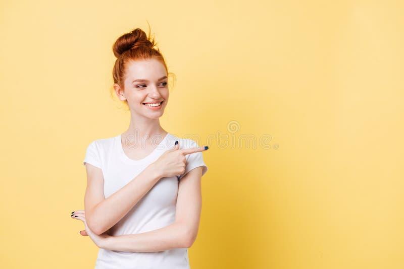 Uśmiechnięta imbirowa kobieta wskazuje daleko od i patrzeje w koszulce fotografia royalty free