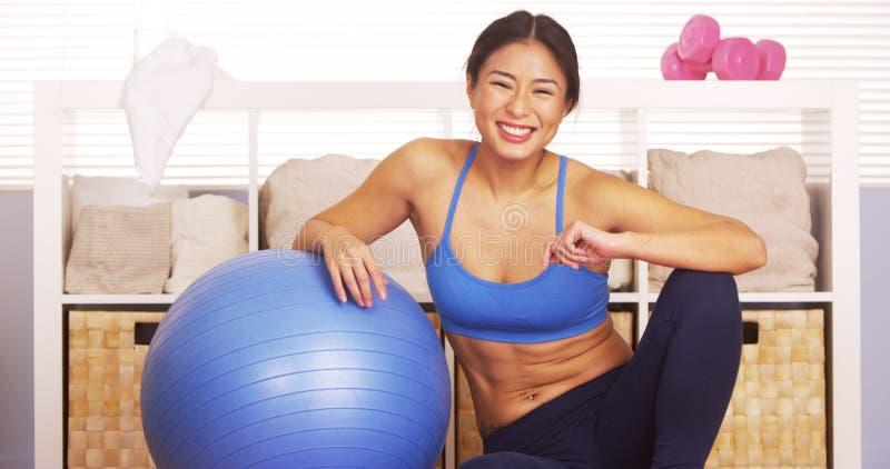 Uśmiechnięta Japońska kobieta odpoczywa na trening piłce zdjęcia royalty free