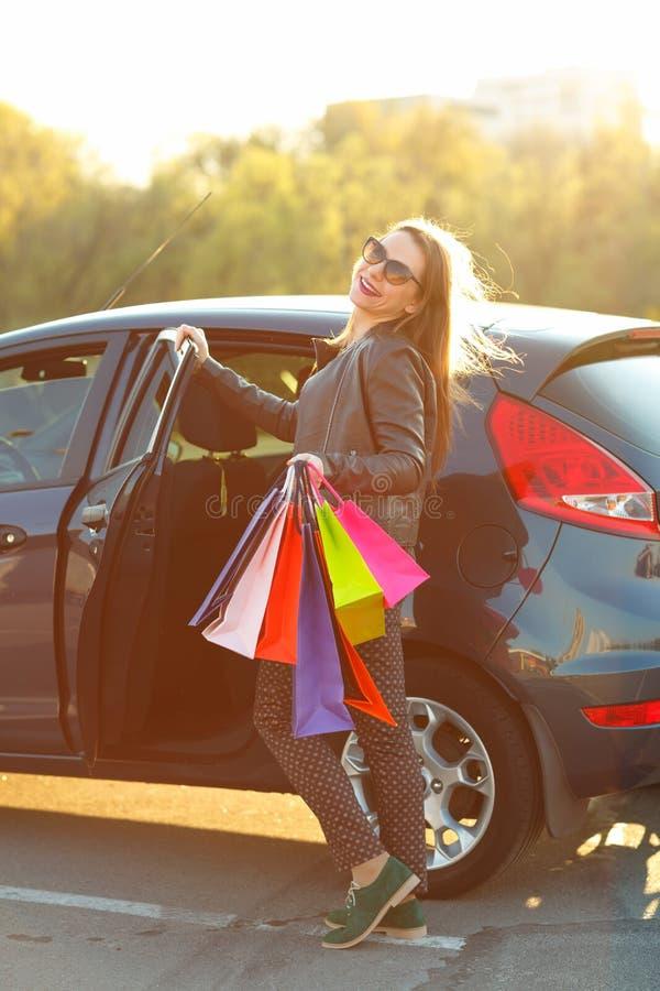 Uśmiechnięta Kaukaska kobieta stawia jej torba na zakupy w samochód obrazy royalty free
