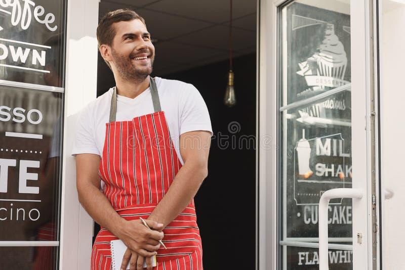Uśmiechnięta kelner pozycja w wejściu sklep z kawą zdjęcia stock