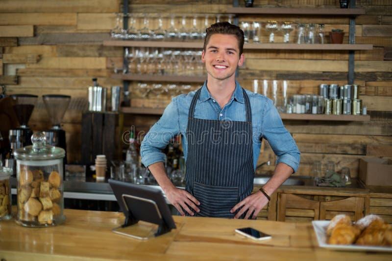 Uśmiechnięta kelner pozycja z rękami na biodrze przy kontuarem zdjęcia royalty free