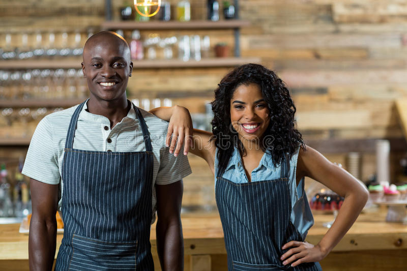 Uśmiechnięta kelnera i kelnerki pozycja przeciw kontuarowi w café obraz stock