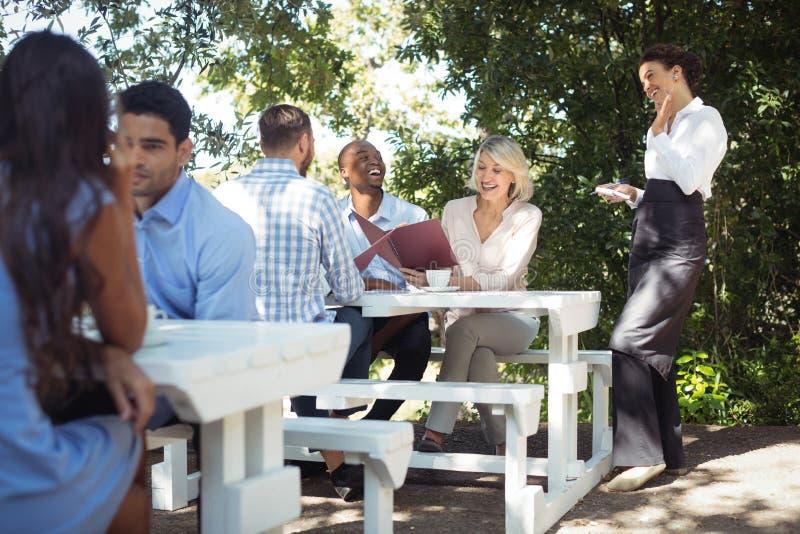 Uśmiechnięta kelnerka bierze rozkaz od klienta w restauraci zdjęcia stock