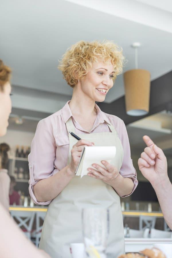 Uśmiechnięta kelnerka bierze rozkaz od mężczyzny obsiadania przy restauracją fotografia stock