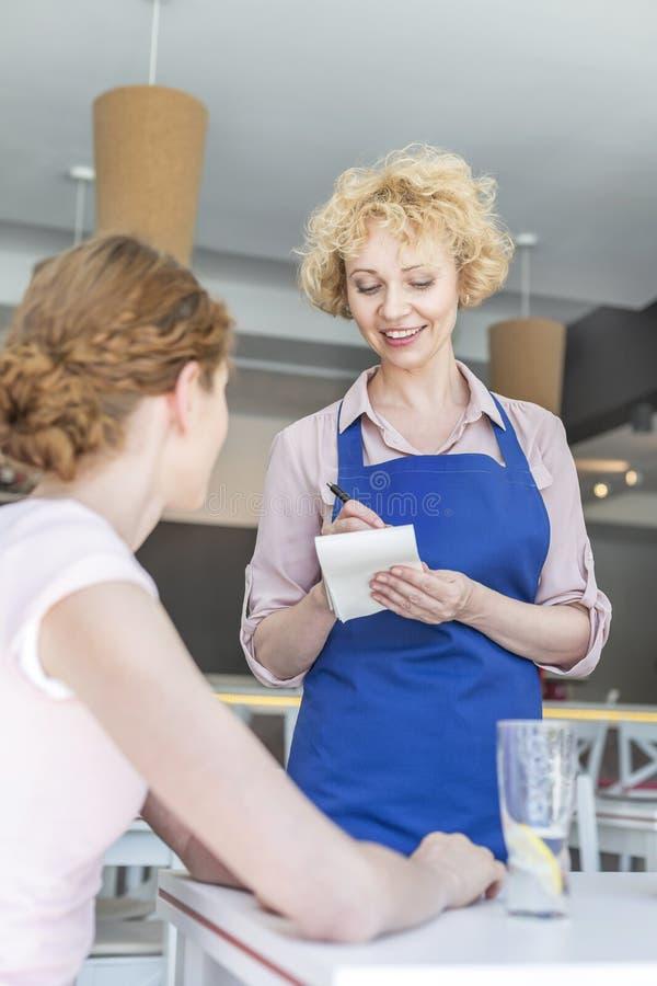 Uśmiechnięta kelnerka bierze rozkaz od młodej kobiety obsiadania przy stołem w restauracji obraz stock