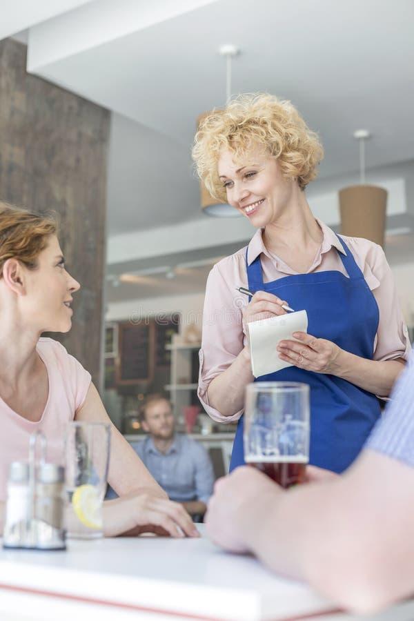 Uśmiechnięta kelnerka bierze rozkaz od młodej kobiety obsiadania z mężczyzną przy restauracją zdjęcia stock