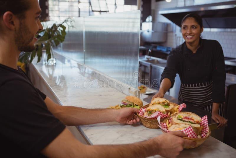 Uśmiechnięta kelnerka daje koszom z jedzeniem coworker w kawiarni obrazy stock
