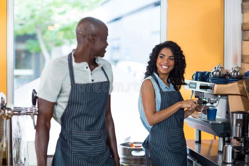 Uśmiechnięta kelnerka i kelner oddziała wzajemnie podczas gdy pracujący przy kontuarem zdjęcie royalty free