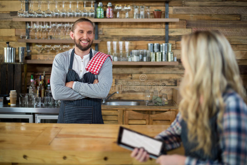 Uśmiechnięta kelnerka i kelner oddziała wzajemnie przy kontuarem obraz royalty free