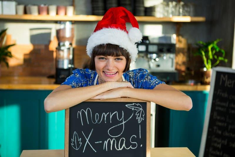 Uśmiechnięta kelnerka jest ubranym Santa kapelusz i obsiadanie z Mas znakiem wsiadamy zdjęcia stock