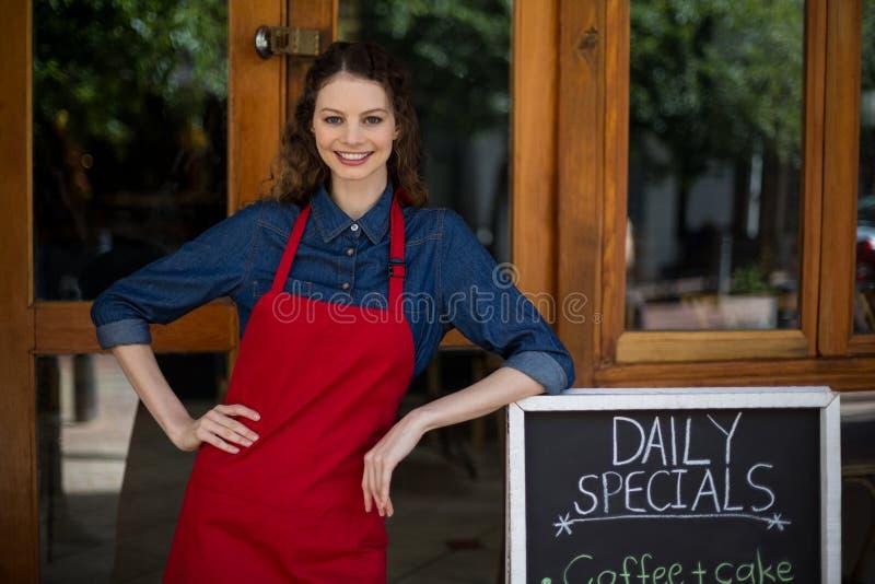 Uśmiechnięta kelnerka opiera na menu desce na zewnątrz kawiarni zdjęcie stock