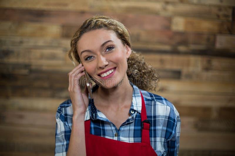 Uśmiechnięta kelnerka opowiada na telefonie komórkowym przeciw drewnianej ścianie obrazy stock