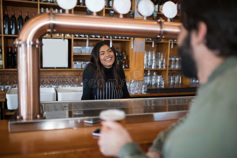Uśmiechnięta kelnerka opowiada obsługiwać przy kontuarem obraz stock