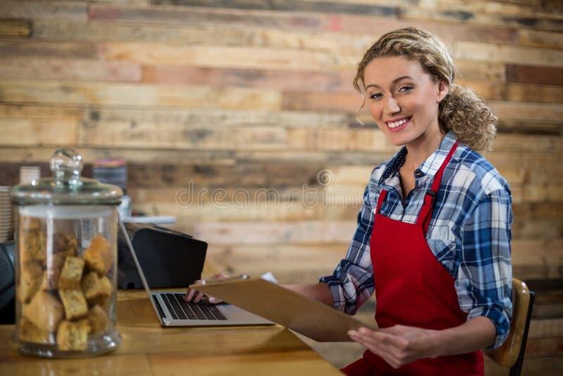 Uśmiechnięta kelnerka patrzeje schowek podczas gdy używać laptop w café obrazy royalty free