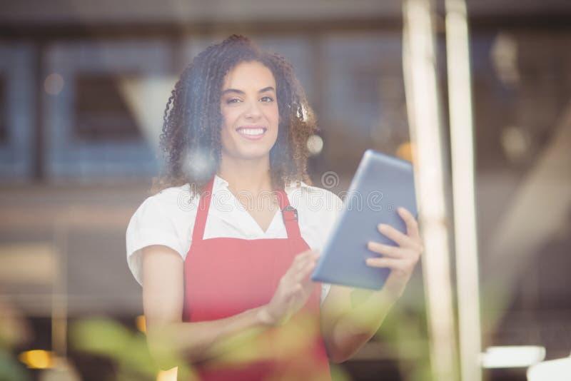 Uśmiechnięta kelnerka używa cyfrową pastylkę fotografia stock