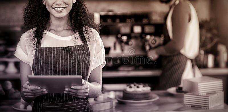 Uśmiechnięta kelnerka używa cyfrową pastylkę przy kontuarem w café obrazy royalty free