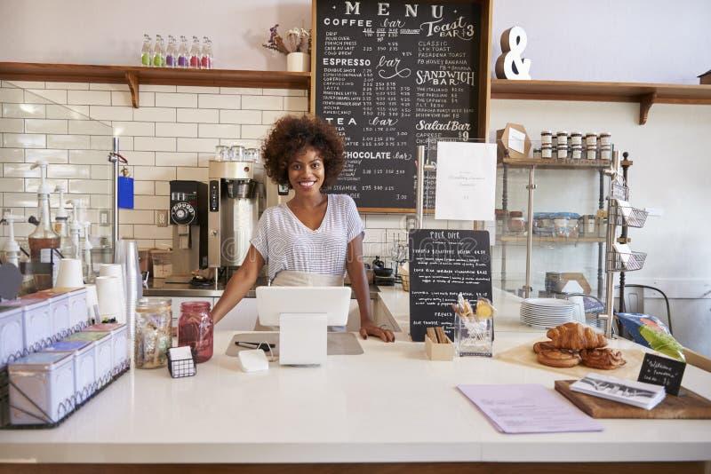 Uśmiechnięta kelnerka za kontuarem przy sklep z kawą obrazy stock