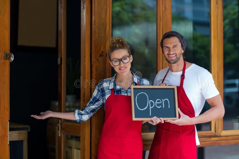 Uśmiechnięta kelnerki i kelnera pozycja z otwartym znakiem wsiada outside café obrazy stock