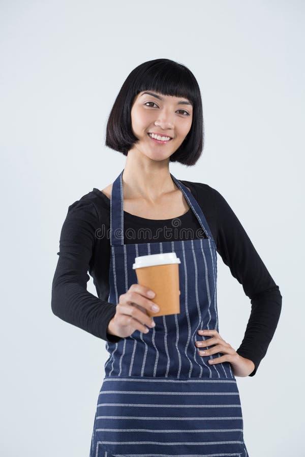 Uśmiechnięta kelnerki porci kawa przeciw białemu tłu fotografia stock