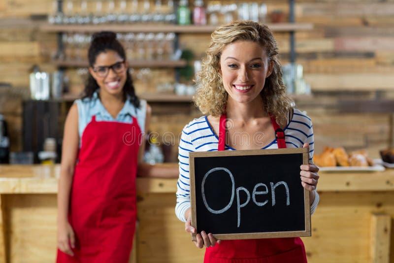 Uśmiechnięta kelnerki pozycja z otwartym signboard w kawiarni fotografia stock