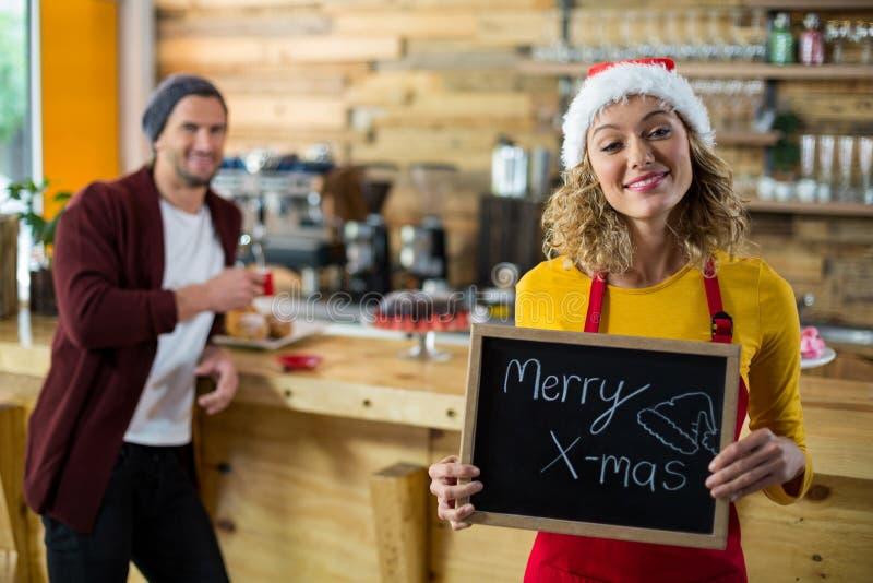 Uśmiechnięta kelnerki pozycja z wesoło x mas znaka deską w kawiarni zdjęcie royalty free