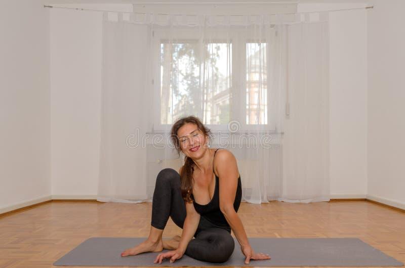 Uśmiechnięta kobieta ćwiczy joga na macie w domu obraz stock