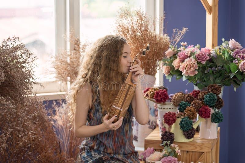 Uśmiechnięta kobieta cieszy się i relaksuje bawić się ukulele w mu zdjęcia stock