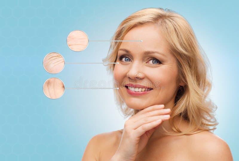 Uśmiechnięta kobieta dotyka twarz z nagimi ramionami obraz stock