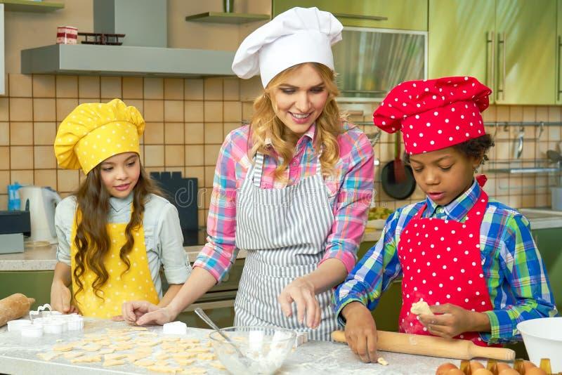Uśmiechnięta kobieta i dzieciaki, kuchnia obraz stock