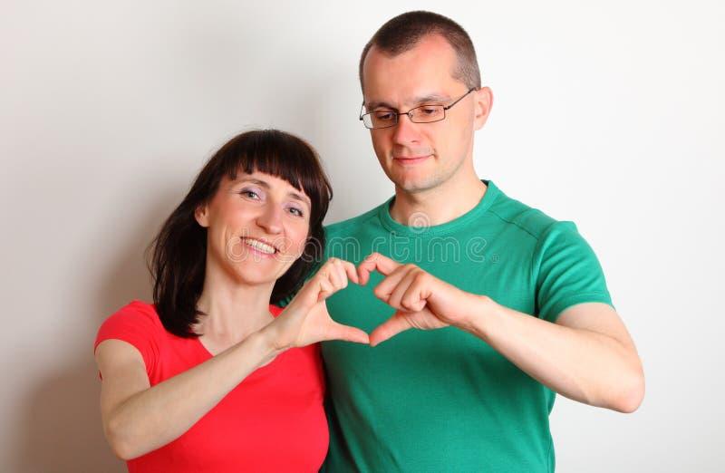 Uśmiechnięta kobieta i mężczyzna z rękami w kierowym kształcie obrazy stock