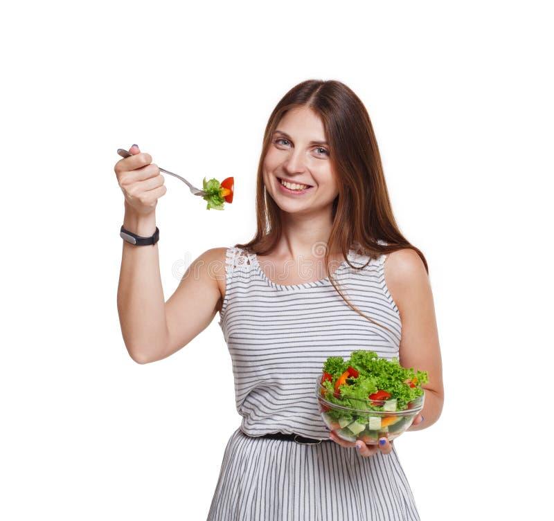 Uśmiechnięta kobieta je świeżego warzywa sałatki odizolowywającej na bielu fotografia stock