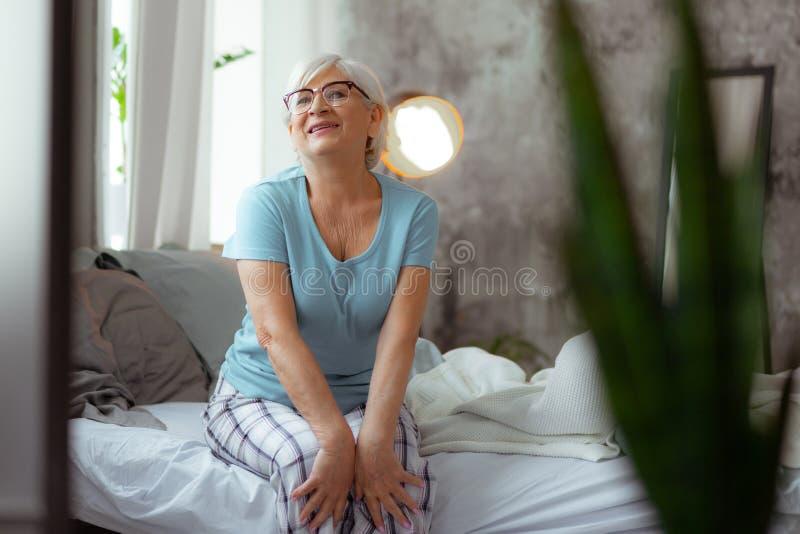Uśmiechnięta kobieta jest ubranym eyeglasses i piżamy obsiadanie na łóżku fotografia stock