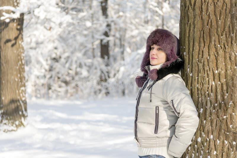 Uśmiechnięta kobieta jest ubranym futerkowego kapelusz stoi w lesie i fotografia stock