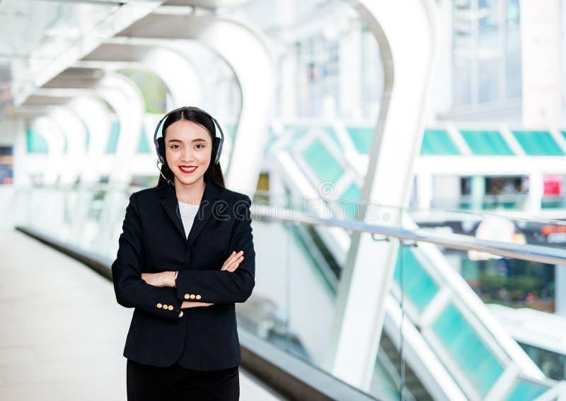 Uśmiechnięta kobieta jest ubranym mikrofon słuchawki jako operator, obraz royalty free