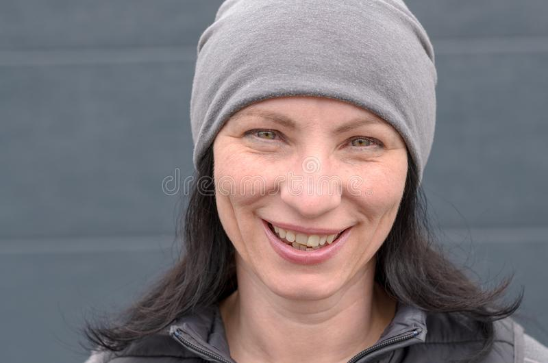 Uśmiechnięta kobieta jest ubranym szarego beanie kapelusz zdjęcia royalty free