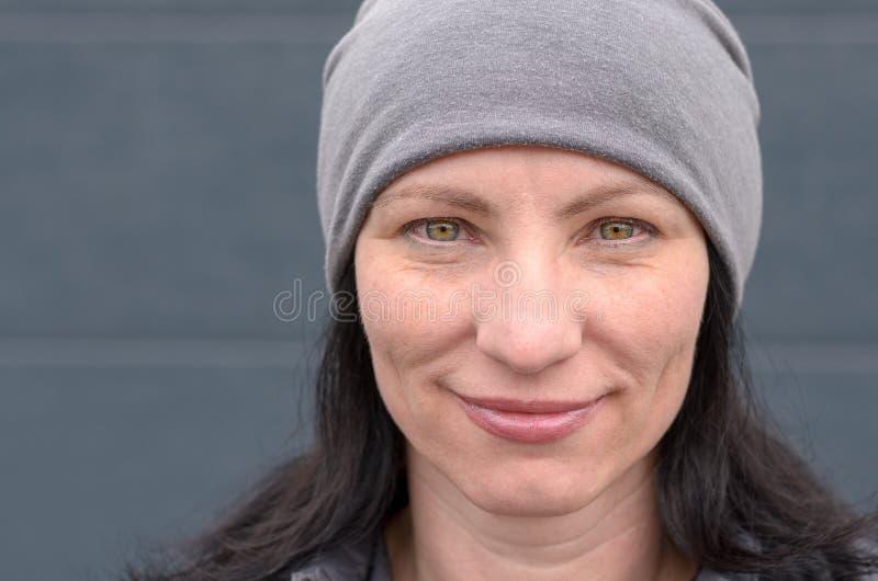 Uśmiechnięta kobieta jest ubranym szarego beanie kapelusz obrazy royalty free