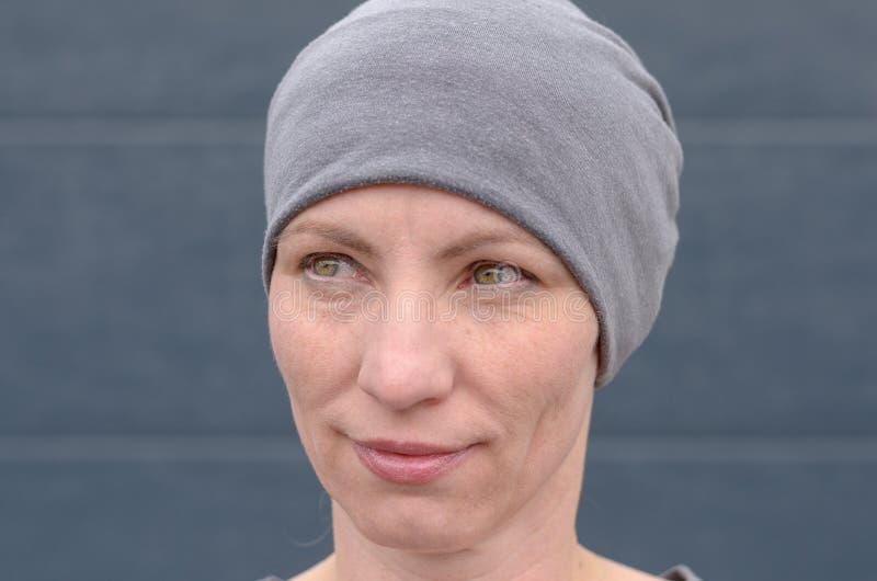 Uśmiechnięta kobieta jest ubranym szarego beanie kapelusz zdjęcia stock