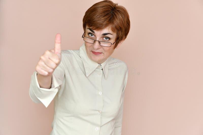 Uśmiechnięta kobieta jest ubranym szkła pokazuje kciuk up obrazy stock