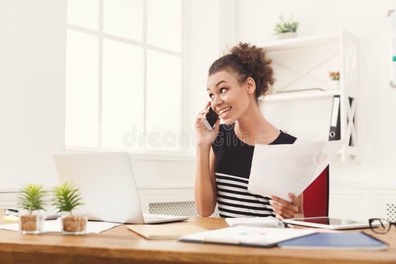 Uśmiechnięta kobieta konsultuje telefonem przy biurem obrazy stock