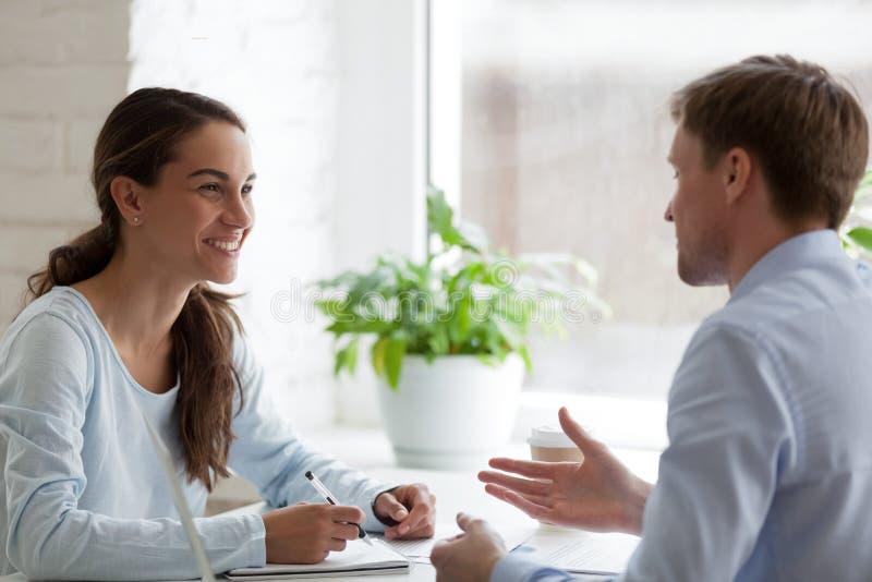 Uśmiechnięta kobieta ma przyjemną rozmowę z męskim kolegą zdjęcia stock