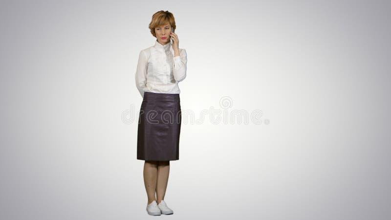 Uśmiechnięta kobieta ma rozmowę telefonicza na białym tle obrazy royalty free