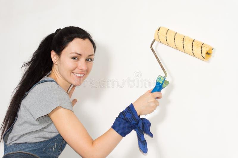 Uśmiechnięta kobieta maluje jej dom zdjęcia stock