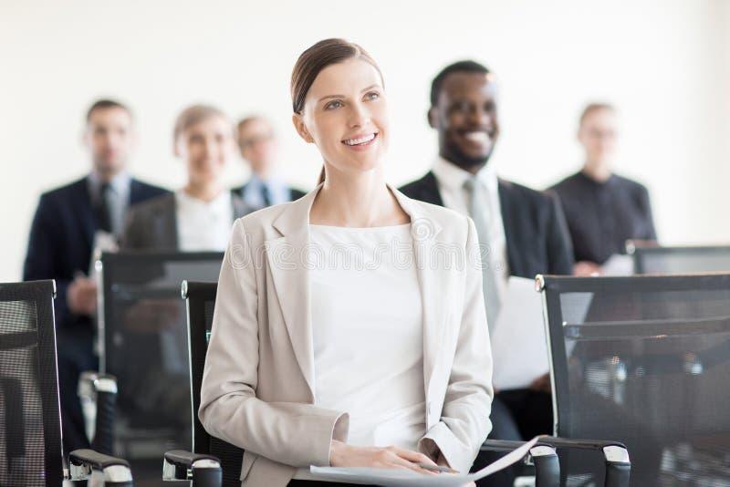 Uśmiechnięta kobieta na konferenci w biurze zdjęcie royalty free