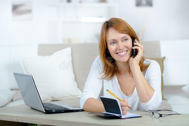 Uśmiechnięta kobieta na rozmowie telefonicza używać laptop fotografia royalty free